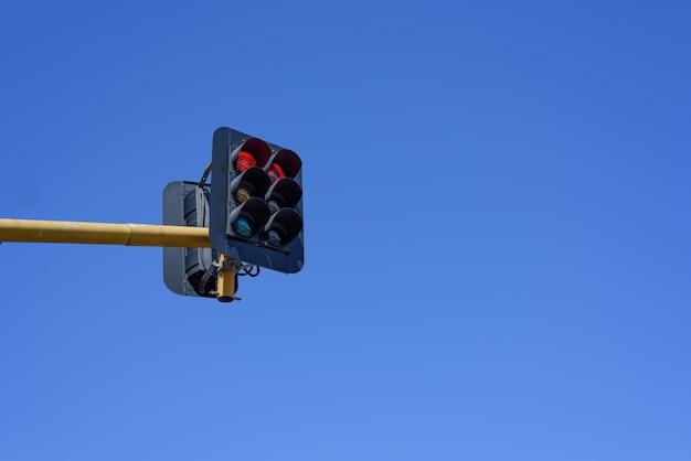 青い空の背景に赤信号
