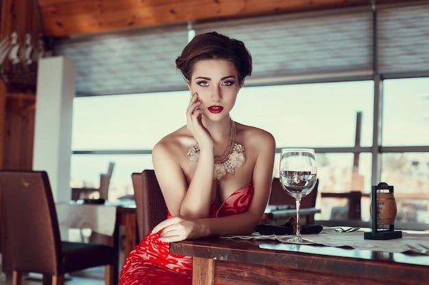 レストランで赤いドレスを着た美しい女性。