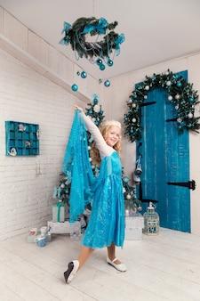 Счастливая маленькая девочка в платье с подарком на рождество