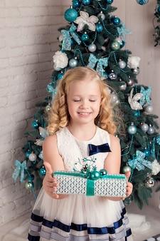 Счастливая маленькая девочка в платье с рождественским подарком