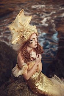 Красивая модная русалка сидит на скале у моря