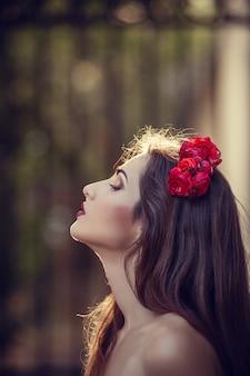 花かざりと夕暮れ時の公園で美しい若いブルネットの女性