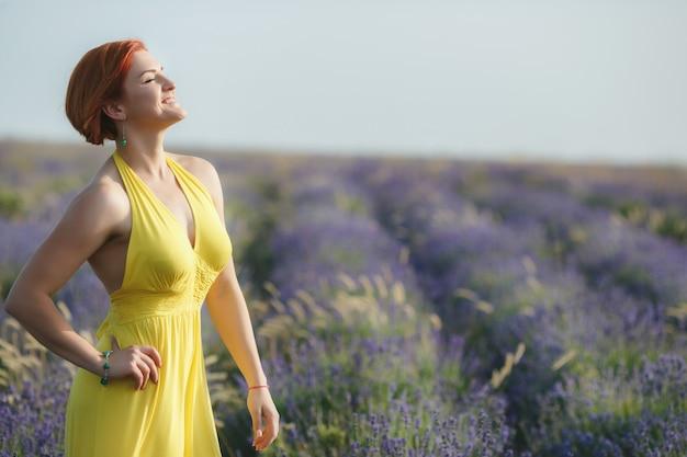 Улыбка красивая брюнетка в сиреневом поле на закате