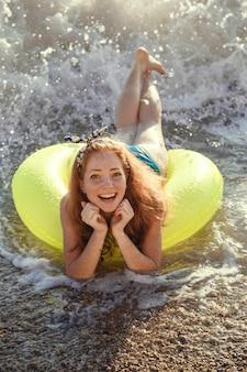 若い美しい女性は、ゴム製のリングが付いているサンセットビーチでリラックスできます。