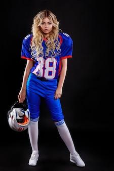 黒の背景にアメリカンフットボールの女の子を装ったアスレチックブロンド。アメリカンフットボールトップホールディングボールを着ている美しい若い女性。アメリカンフットボールの女性のスタジオ写真