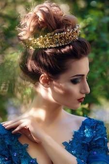 緑の高級高価なドレスと自然の王冠の美容女性。緑のウェディングドレスの美しいモデルの女の子。公園の女性の肖像画。髪型を持つ女性。かわいい女性アウトドア