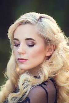 頭の周りのファッショナブルな髪乱れた三つ編み。夏の花公園で幸せな美しい若いモデルの女の子。