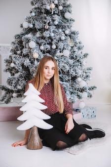 クリスマスギフト。新年のお祝い。その下にプレゼントをクリスマスツリーが飾られた美しい休日の部屋。新年とクリスマスの概念。新年の木の近くに座っている美しい少女。