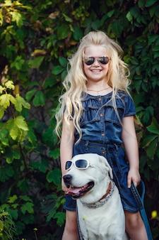 Красивая блондинка, играя со своей собакой. открытый портрет. серии