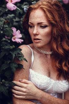長いウェーブのかかった赤い髪の若い美しいセクシーな女性のファッションの肖像画。白いブラジャーや夏の庭でランジェリーでかわいい女の子。ファッションスタイルのトーンの色の肖像画。