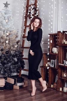 Рождество санта красивая улыбающаяся женщина модель. составить. здоровая длинная прическа. элегантная дама в черном платье на фоне огней елки. с новым годом