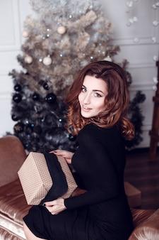 クリスマスサンタ。美しい笑顔の女性モデル。化粧。健康なロングヘアスタイル。クリスマスツリーライトの背景に黒のドレスでエレガントな女性。明けましておめでとうございます