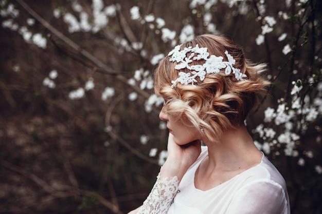 Молодая красивая блондинка женщина в цветущем саду.
