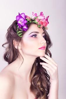 彼女の髪に花を持つ美しい笑顔の女の子