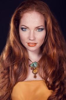 長い巻き毛の赤い髪。ファッション女性の肖像画。豪華な髪、メイクアップ、アクセサリーの美少女モデル。髪型。ウェーブヘアエクステンションのコンセプトです。休日メイク。