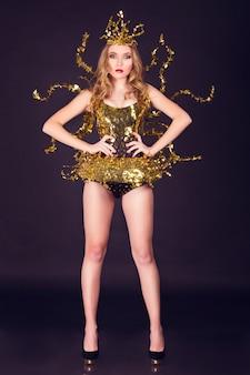 金属の翼を持つユニークな黄金の衣装を着たセクシーなディスコパーティーの女性。スタイリッシュなクラブ、ディスコ、ファッションイベントに最適
