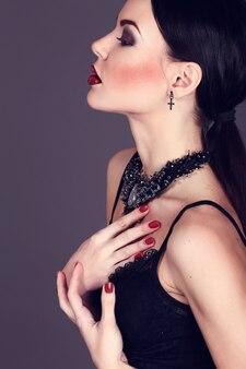 Красивая женщина с темными волосами и вечерний макияж. ювелирные изделия и красота.