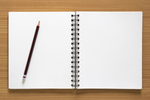 空の螺旋状のメモ帳と木製の鉛筆の背景