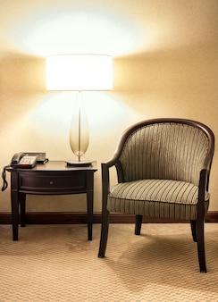 夜の寝室で木製の椅子とテーブルランプ