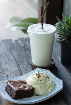 ホイップクリームとお茶をテーブルの上のブラウニーケーキ
