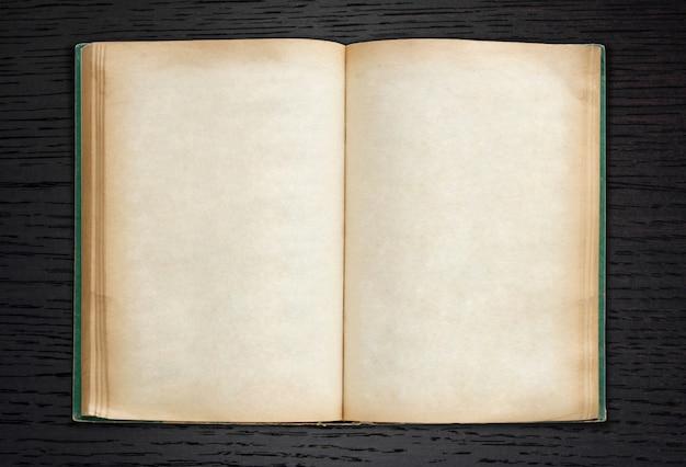 古い本は暗い木の背景に開く
