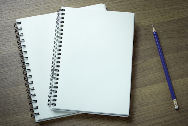 空の螺旋状のノートブックと鉛筆の暗い木の背景
