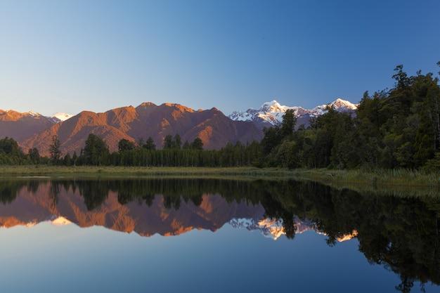 ツインピークスは、ニュージーランドの日没で美しいマセソン湖に反映します。