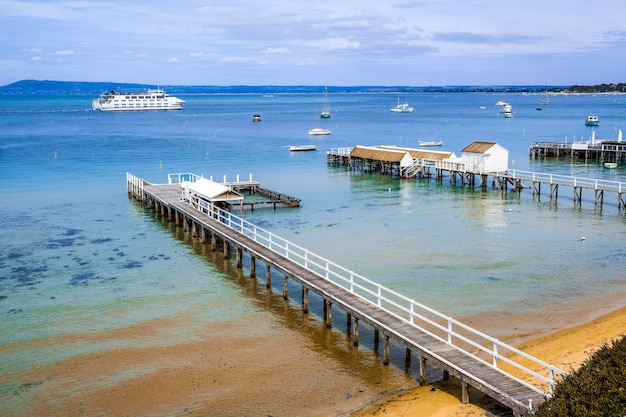 沿岸の風景-浅い湾の水に伸びる木製の桟橋があり、遠くを航行する旅客フェリーがあります。メルボルン、ビクトリア、オーストラリア