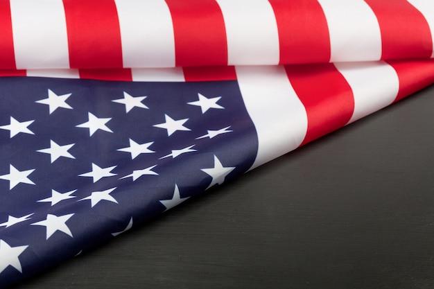 Сложенный американский флаг на черной доске с копией пространства.