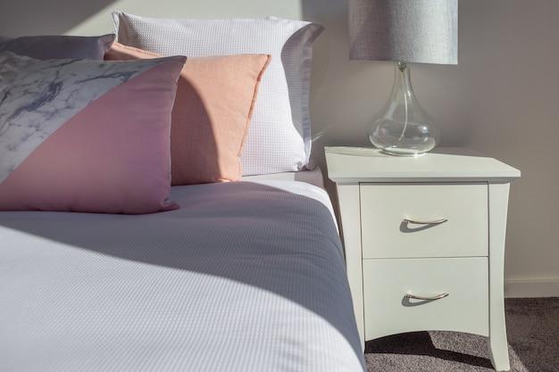 白いベッドサイドテーブルと寝室のランプのクローズアップとベッドの上の枕