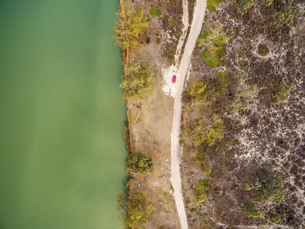 南オーストラリア州のマレー川の岸に駐車した小さな赤い車を見下ろして