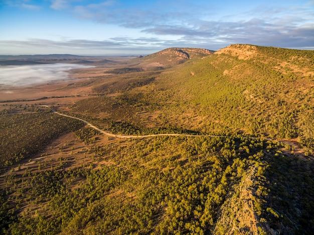 険しい崖と朝日の低い雲の下の曲がりくねった道。ジャービスヒル展望台、ホーカー、南オーストラリア州