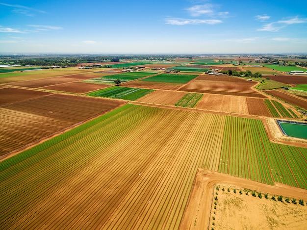 農地の空撮。耕作され、オーストラリアの明るい夏の日に作物