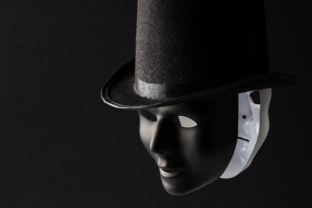 黒いシルクハットを身に着けている黒と白のマスク