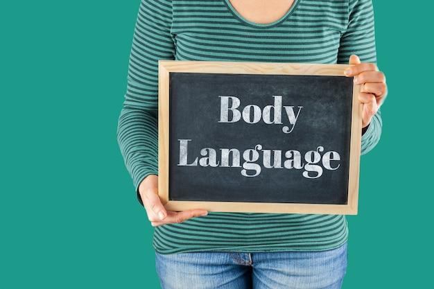 体の言語を言って書かれた言葉で体の前に小さな黒い黒板を保持している女性の手
