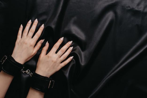 暗い絹のシートに手錠をかけられて女性の手
