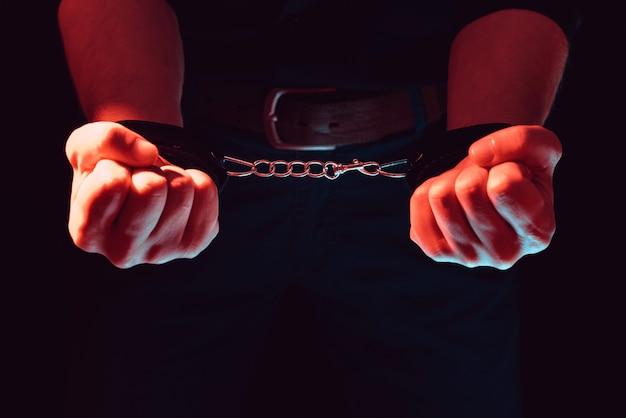 セックスのために黒い毛皮のような革製の大人のおもちゃの手錠を身に着けている男の手。