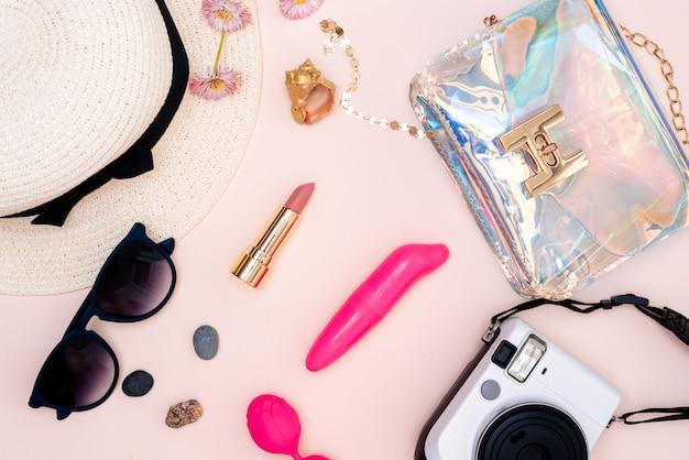 Женский набор игрушек для взрослых, фотоаппарат, шапка, очки и вид сверху на светлом столе.