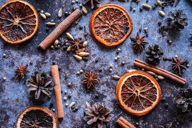Натюрморт с набором для глинтвейна. сушеный апельсин, палочки корицы, розовый перец, кардамон, анис, гвоздика на синем фоне. вид сверху