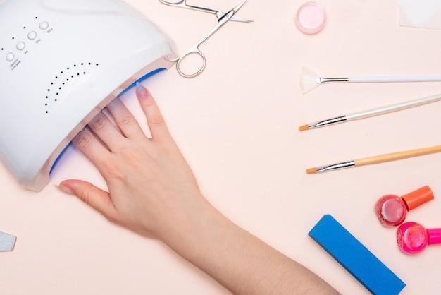 女の子の爪は紫外線ランプで乾かされます。上からの眺め