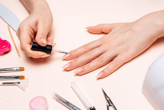 マニキュア。女の子が爪を塗ります。手がクローズアップ