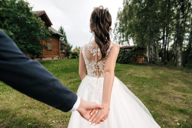 私のコンセプトに従ってください。自然のフィールドで彼氏の手を握っている女の子の裏