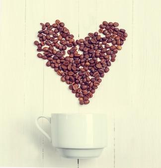 Вид сверху зерна кофе в форме сердца над чашкой.