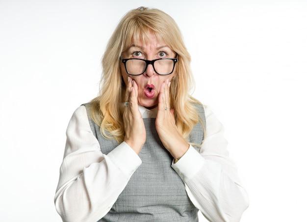 Удивлен зрелая женщина в очках жесты ее эмоции на светлом фоне.