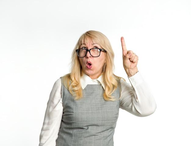Взрослая женщина в очках показывает вверх на светлом фоне.