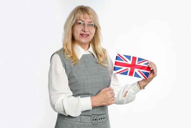 明るい背景にイギリスの旗を持つ成熟した女性。