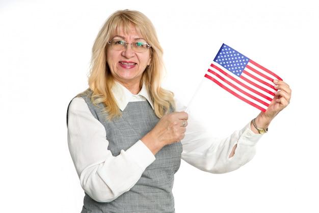 白い背景で隔離のアメリカ合衆国の旗と幸せな成熟した女性。