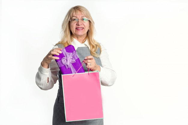 ピンクのパッケージと白の紫色のボックスにギフトを持つ成熟した女性。