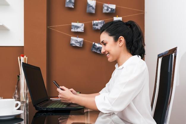 自宅でその場しのぎのオフィスで彼女の携帯電話をチェックする若いラティーナ女性。