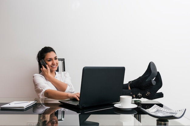 Женщина работает из дома с ее ноутбуком, говорить по мобильному телефону с ее ноги на столе